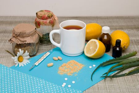 tea with lemons, aloe vera, cooler and medications for seasonal colds, drops, iodine, pills on a blue background, gray wooden table, front view
