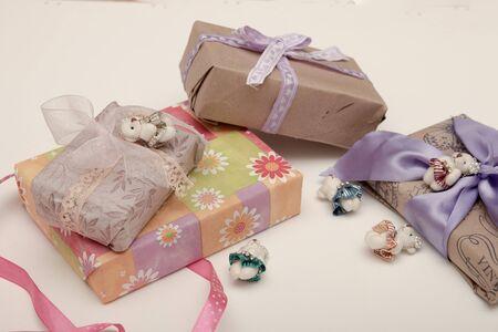 在白色的背景下,包装着棕色的礼物,带着明亮的丝带和蝴蝶结,母亲节,感恩节,礼物