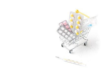 medicines in a shopping trolley and mercury thermometer on a white background copy space Zdjęcie Seryjne