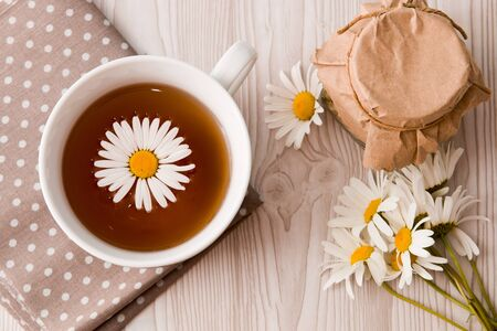 cup of tea and camomile and jar on a polka dot fabric tea can lace grey brown orange beige fliwers Zdjęcie Seryjne