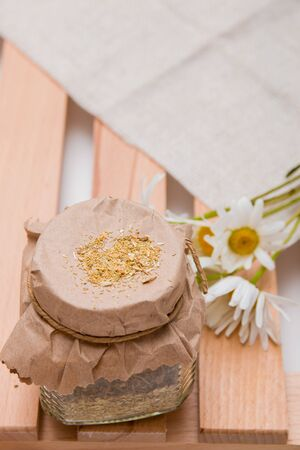a jar of herbal tea stands on a wooden tray of rekk with a daisy flower and a beige coarse cloth copy space top view