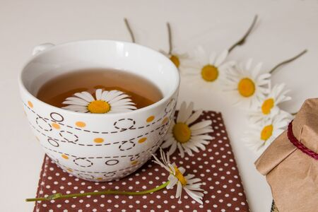 cup of tea on brown polka dot fabric with camomile on a white background Zdjęcie Seryjne