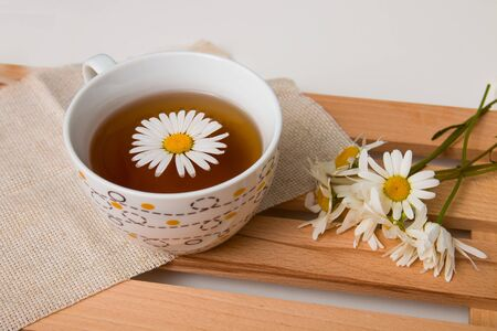 cup with chamomile tea on a beige fabric with daisies on a wooden tray white background isolation top view copy space