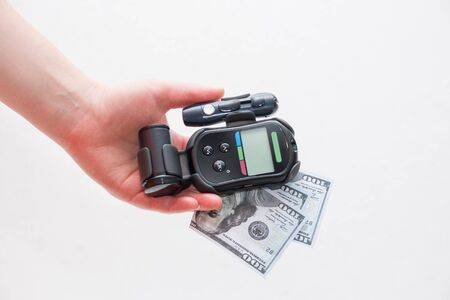 female hand holds a black glucometer and several notes of 100 dollars, white background Stock Photo
