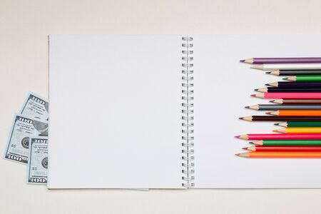 colored pencils lie on a white notebook with a spring and readable sheets of dollars banknotes money on a white table pencil sharpening sharpen color top view spring copybook copy space