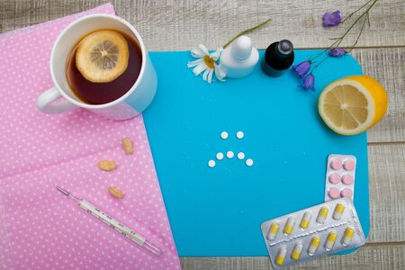 sad face made of pills on a blue background, lemon tea, different pills and medicines for treating colds 스톡 콘텐츠