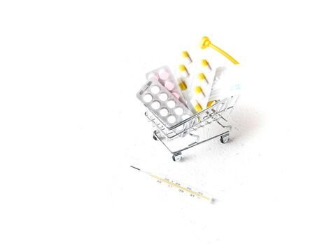 syringe, pills in a shopping trolley and mercury thermometer on a white background copy space