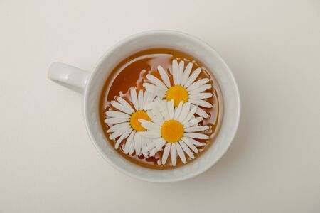 chamomile in a cup of tea on a white background isolation top view place copy chamomile flowers