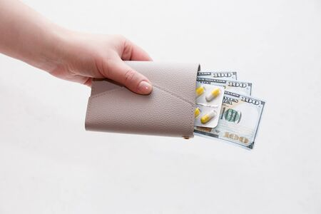 female hand holds a wallet with yellow capsule pills and dollar bills, white background Stock Photo