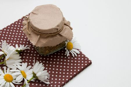 tea can covered with paper tied with a lace, camomiles,on a brown cloth in a pot on a white table top view copy space isolation flowers Zdjęcie Seryjne