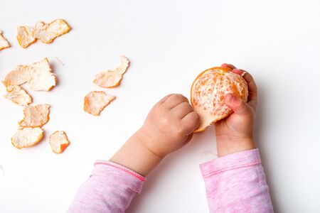 children's hands peel mandarin on a white background pink orange Banco de Imagens