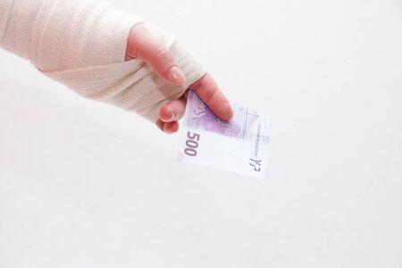 bandaged female hand holds a 500 euro bill