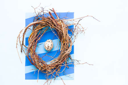 one quail egg in a nest of branches, blue striped background, light blue background for your congratulations, copy space, top view, original Easter card
