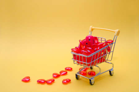 shopping trolley full of red hearts, one bigger sweetheart heart, on a yellow background, copy space, shopping for a holiday, Valentine's Day greetings, holiday shopping