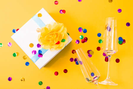 silver shiny box decorated with a yellow flower of delicate fabric and two glasses for champagne, yellow background strewn with confetti, copy space, top view