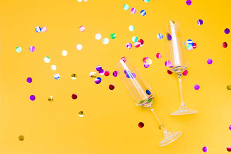 two glass champagne glasses on a yellow background strewn with confetti, shiny circles in the glasses, Valentine's day concept, wedding day, lovers' date, copy place
