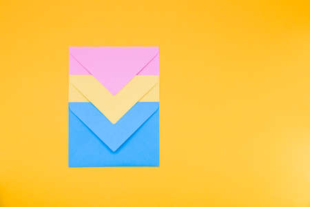 three envelopes of yellow, blue and pink colors nested in each other lie on a yellow background copy space top view, minimalism concept for congratulations 免版税图像