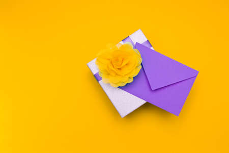 a purple envelope lies under a silvery shiny box with a purple ribbon and a large yellow flower of light delicate fabric, yellow background, copy space, top view