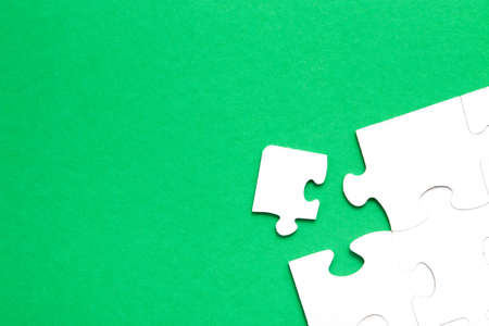 unfinished puzzle made of white cardboard on a green background and one unsuitable part from another puzzle, one piece is missing, copy space, search for some suitable part, team building concept