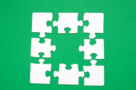 unfinished puzzle made of white cardboard on a green background and one unsuitable part from another puzzle, one piece is missing, copy space, search for some suitable part