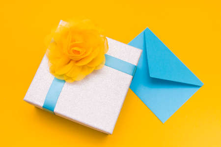 a blue envelope lies under a silver shiny box with a blue ribbon and a large yellow flower of light delicate fabric, yellow background, copy space, top view
