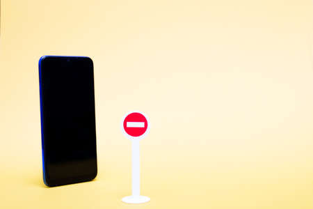 toy stop sign and smartphone on a yellow background, digital detox concept, copy space Stockfoto