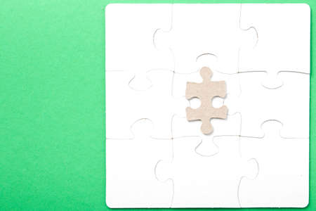 the detail from the brown cardboard puzzle lies on the folded white puzzle, the detail is different, not suitable, the concept of difference, stand out from the crowd, not be like everyone else, state of mind