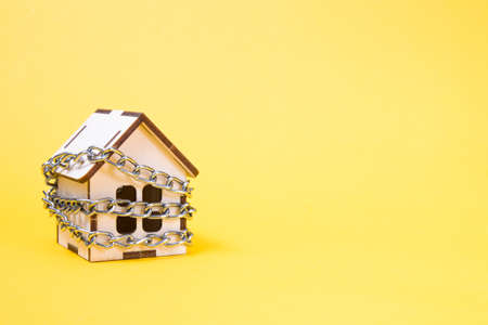 small wooden decorative wrapped in silver chain on a yellow background, real estate protection concept, home insurance