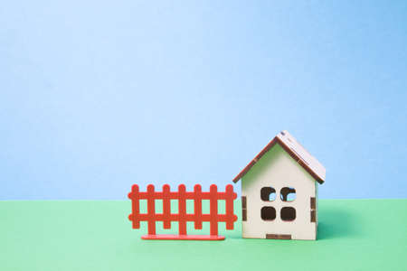 wooden toy house from the constructor for children, brown fence on a blue background, green background, copy space
