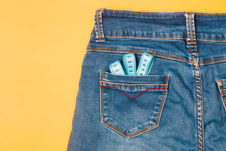 blue measuring tape in the back pocket of jeans, blue jeans on a yellow background, copy space, weight loss and weight control concept, measuring body volume