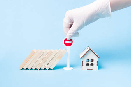 hand in a white medical rubber glove stops a domino using a miniature stop road sign, wooden house model, blue background, self-isolation and quarantine concept, stop a pandemic, stay home Banque d'images