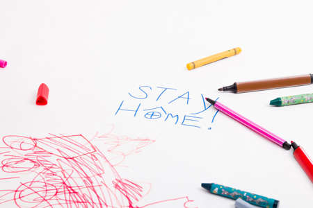 inscription on white paper stay home, felt-tip pens and wax crayons lie on drawing paper, child's drawing, activities with the child during quarantine, development of children