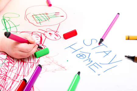 a small child draws with a felt-tip pen on paper, what to do with the child during quarantine, the development of preschool children, the inscription stay home on a sheet of paper, focus on the inscription