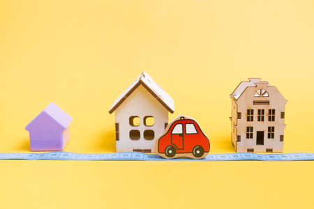several models of houses on a yellow background, measured blue tape for measuring distance, red car toy, social distance during quarantine, stay at home concept, copy space