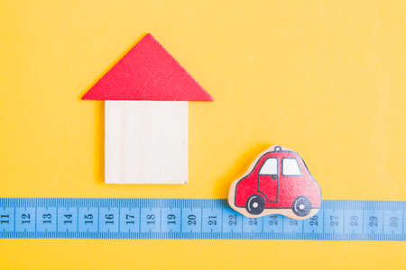 wooden house made of trugolnik and square and next to it is a toy red car, measuring tape on a yellow background, social distance concept, krantin and pandemic 2020