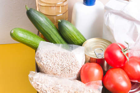 box with products for donation, yellow background, copy space, cereals, vegetables, fruits, oil in a bottle, flour and canned food in a box, hygiene product and protection against coronavirus