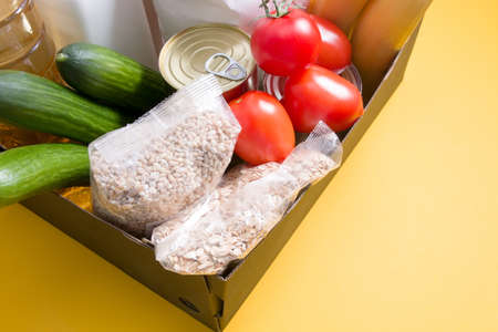 box with products for donation yellow background, copy space, cereals, vegetables, fruits, oil in a bottle, flour and canned goods in a cardboard box, volunteering concept Banque d'images