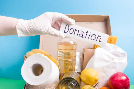 hand in a white rubber glove puts a white cardboard box with donation inscription in a food box on a blue-green background, help with a coronavirus pandemic, volunteer concept