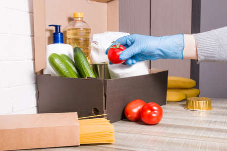 a woman in a rubber glove sweetens a red tomato in a box with products for donation, help during the coronavirus pandemic 2020, delivery contactless concept Banque d'images