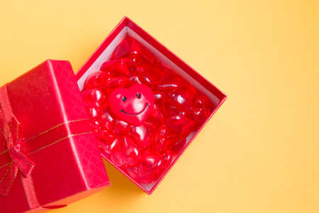 many small glass red hearts and a heart with a smile in a gift red box, yellow background