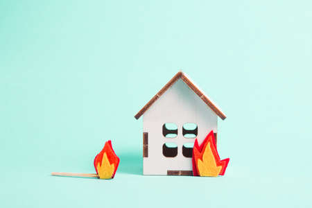 burning wooden model of a house, fire cut out of felt, blue background copy space, insurance and protection of real estate concept, a match lies nearby, arson of a house