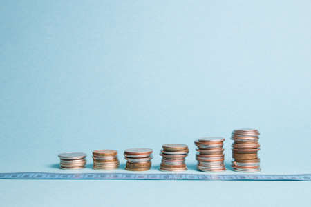 several towers of coins and a blue measuring tape, blue background, copy space, financial growth concept, profit and earnings growth, anti-crisis actions Stockfoto