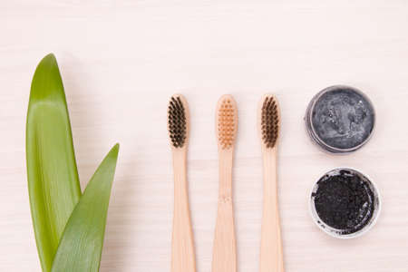 bamboo toothbrushes on natural coarse cloth on a wooden table, homemade charcoal toothpaste in a small glass jar, leaves long plants, eco friendly life style concept Stock Photo