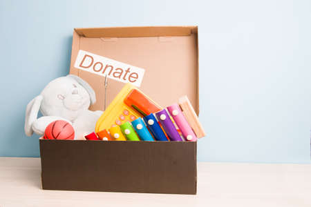 children's toys in an open cardboard box with a lid on a light wooden table, light blue background, copy space, donation box concept, donate inscription on a white cardboard Foto de archivo