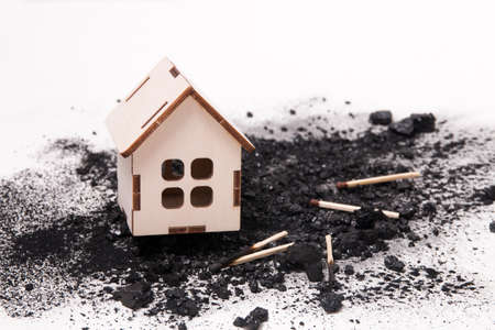 wooden house model on a pile of coal and matches, white background copy space, real estate fire insurance concept