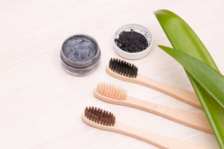 bamboo toothbrushes on a wooden table, homemade charcoal toothpaste in a small glass jar, leaves long plants, eco friendly life style concept, zero waste 版權商用圖片