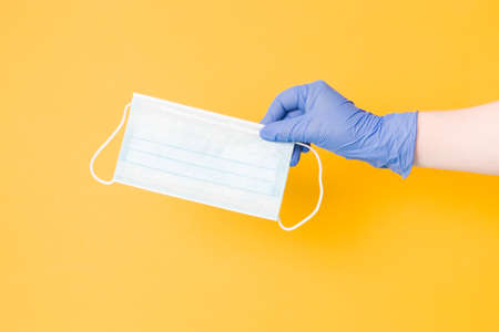 hand in blue disposable glove holds protective medical face mask, yellow background, copy space
