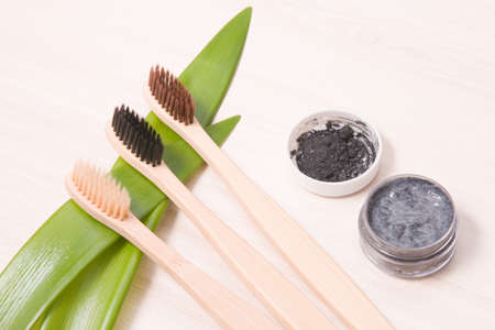 bamboo toothbrushes on a wooden table, focus on a brush with black bristles, homemade charcoal toothpaste in a small glass jar, leaves long plants, eco friendly life style concept