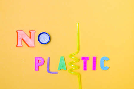 inscription from plastic letters and waste - no plastic, instead of letters a bottle from a bottle and cocktail tubes, yellow background, copy space, top view