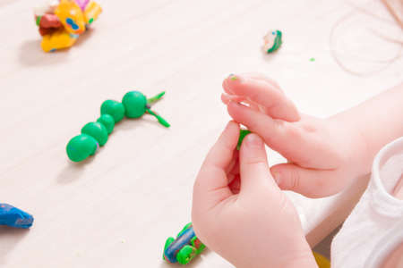a small child sculpts from plasticine on a wooden table, the development of fine motor skills of hands, than to occupy a child at home, stay at home
